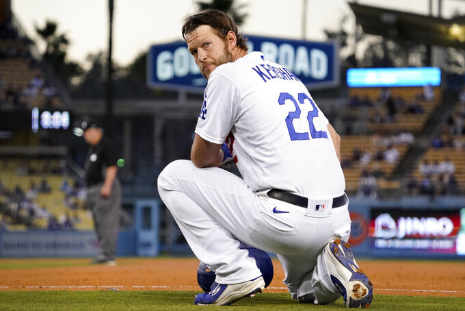 Los Angeles Dodgers' Clayton Kershaw kneels at first as he waits for a pitching change during the third inning of a baseball game against the Texas Rangers Friday, June 11, 2021, in Los Angeles. (AP Photo/Mark J. Terrill)