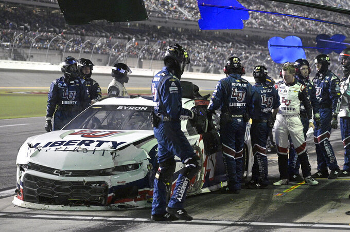 William Byron, right, looks on as crew members work on his car on pit road during a NASCAR Cup Series auto race at Daytona International Speedway, Saturday, Aug. 28, 2021, in Daytona Beach, Fla. (AP Photo/Phelan M. Ebenhack)