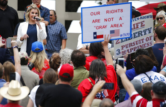 Shelley Luther, owner of Salon Á la Mode in Dallas speaks to the crowd during the Set Texas Free Rally at Dealey Plaza in Dallas, on Saturday, May 9, 2020. (Vernon Bryant /The Dallas Morning News via AP)