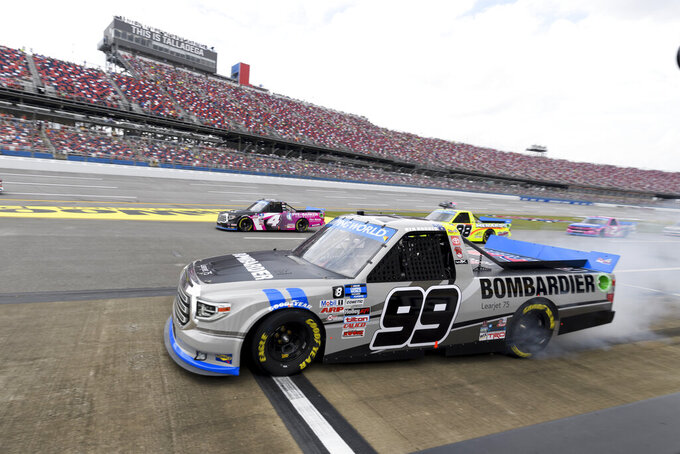 Ben Rhodes (99) pulls away from a pit stop during the NASCAR Truck Series auto race Saturday, Oct. 2, 2021, in Talladega, Ala. (AP Photo/John Amis)
