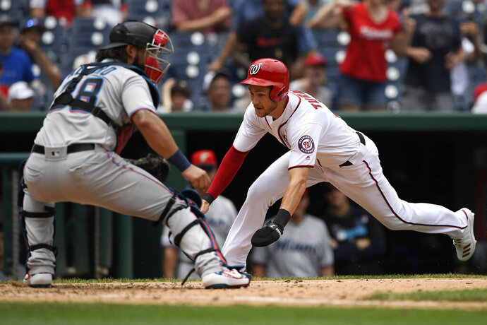 Washington Nationals' Trea Turner, right, comes home to score on a double by Gerardo Parra against Miami Marlins catcher Jorge Alfaro (38) during the sixth inning of a baseball game, Thursday, July 4, 2019, in Washington. The Nationals won 5-2. (AP Photo/Nick Wass)