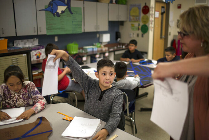 FILE - In this March 31, 2017, file photo a fifth grade student shows his geometry work to a teacher at Columbus Elementary School, in Columbus, N.M. New Mexico's elementary school students may be falling further behind, according to a review of preliminary academic data by legislative analysts that shows less than one-third of students are proficient. In 2020, students faced school closures, were absent more frequently, and had limited access to online learning. (AP Photo/Rodrigo Abd, File)