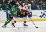 Dallas Stars right wing Alexander Radulov (47) and Calgary Flames defenseman Mark Giordano (5) battle for the puck during the second period of an NHL hockey game in Dallas, Thursday, Oct. 10, 2019. (AP Photo/Michael Ainsworth)