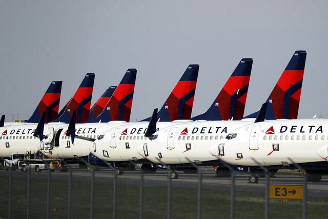"""FILE - In this April 1, 2020, file photo, several dozen Delta Air Lines jets are parked at Kansas City International Airport  in Kansas City, Mo. A sign of the deepening slump in air travel with coronavirus cases rising across the country, Delta CEO Ed Bastian said Wednesday, Dec. 9, 2020, that Delta will need more employees to take unpaid leave """"for the foreseeable future."""" Unlike American and United, Atlanta-based Delta has avoided furloughs since the pandemic started by convincing thousands of workers to retire early or take unpaid leave. (AP Photo/Charlie Riedel, File)"""