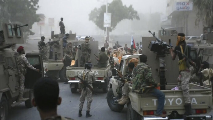 In this Friday Aug. 9, 2019 frame grab from video, Southern Transitional Council separatist fighters line up to storm the presidential palace in the southern port city of Aden, Yemen. The separatists backed by the United Arab Emirates began withdrawing Sunday from positions they seized from the internationally-recognized government in Aden. Both the southern separatists and the government forces are ostensibly allies in the Saudi-led military coalition that's been battling the Houthi rebels in northern Yemen since 2015, but the four days of fighting in Aden have exposed a major rift in the alliance. (AP Photo)