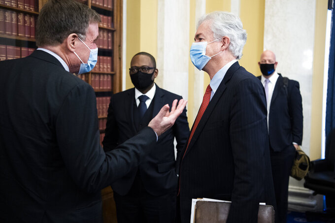William Burns, nominee for Central Intelligence Agency director, talks with Chairman Mark Warner, D-Va., after his Senate Select Intelligence Committee confirmation hearing, Wednesday, Feb. 24, 2021, on Capitol Hill in Washington. (Tom Williams/Pool via AP)