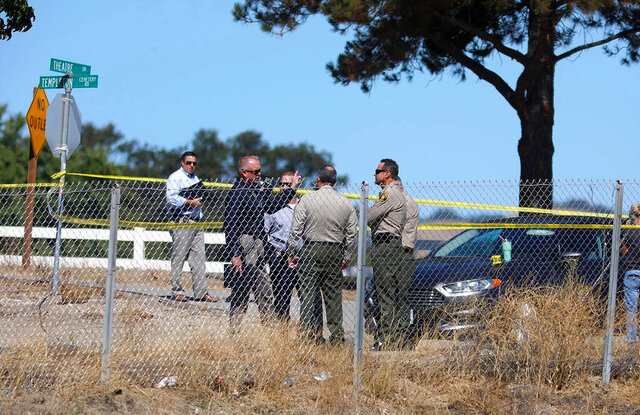 Investigators gather near the shooting scene in which a man was killed by sheriff's deputies after he shot and wounded a deputy in Paso Robles, Calif., Thursday, Sept. 24, 2020. The suspect has been identified as a convicted felon and white supremacist gang member. Officials say the man opened fire on deputies while hiding behind bushes after he ran from his vehicle in Paso Robles.  (Laura Dickinson/The Tribune (of San Luis Obispo) via AP)