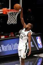 Milwaukee Bucks forward Khris Middleton dunks the ball during the first half of an NBA basketball game against the Brooklyn Nets, Monday, Jan. 18, 2021, in New York. (AP Photo/Adam Hunger)