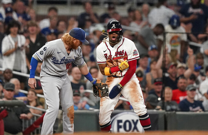 Atlanta Braves' Ronald Acuna Jr., right, reacts after sliding safely into third against Los Angeles Dodgers third baseman Justin Turner (10) in the seventh inning of a baseball game Saturday, June 5, 2021, in Atlanta. (AP Photo/Brynn Anderson)