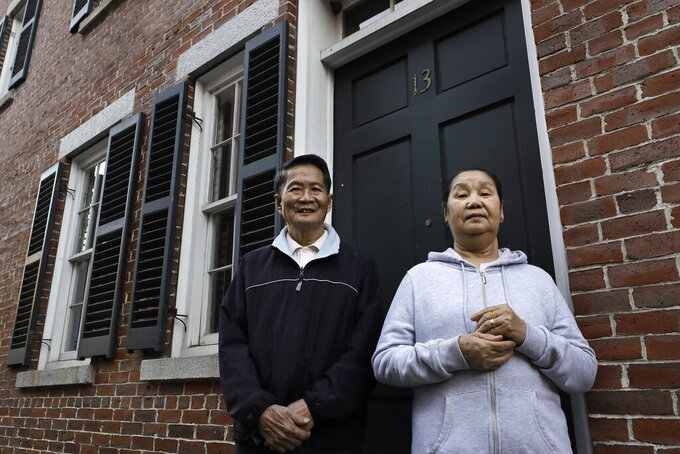 In this Wednesday, May 20, 2020 photo Pay Reh, left, and Poe Meh, right, originally of Burma, also known as Myanmar, stand for a photograph at the entrance to their home, in Lowell, Mass. The elderly couple, who came to Massachusetts as refugees in 2011, were granted a special naturalization oath ceremony in May of 2020 after their lawyer argued that they faced financial hardship if they weren't naturalized immediately. (AP Photo/Steven Senne)