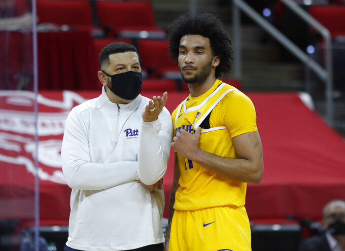 Pittsburgh's head coach Jeff Capel talks with Justin Champagnie (11) after a technical was assessed during the first half of an NCAA college basketball game in Raleigh, N.C., Sunday, Feb. 28, 2021. (Ethan Hyman/The News & Observer via AP)