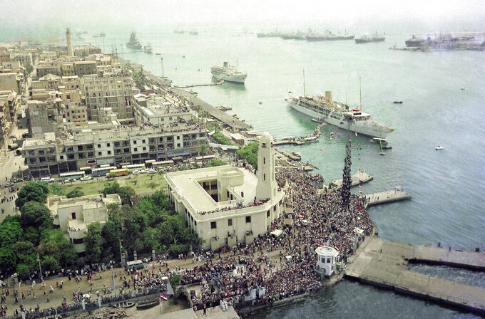 FILE - In this June 5, 1975 file photo, thousands throng the docks and quays of Port Said at the northern end of the Suez Canal in Port Said, Egypt, as the first passenger ships let off steam and pontoon ramps are kicked away as they get ready for first passage through the canal in years. Since it opened in 1869, the canal has been a source of national pride and a focus of international conflict. Now, a skyscraper-sized container ship called the Ever Given got stuck sideways across the waterway since Tuesday, March 23, 2021 . The obstruction has halted canal traffic, valued at over $9 billion a day. (AP Photo/Horst Faas, File)