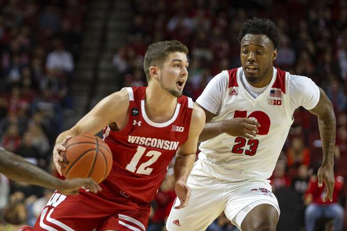 Wisconsin guard Trevor Anderson (12) drives to the basket against Nebraska guard Jervay Green (23) during the first half of an NCAA college basketball game in Lincoln, Neb., Saturday, Feb. 15, 2020. (AP Photo/John Peterson)