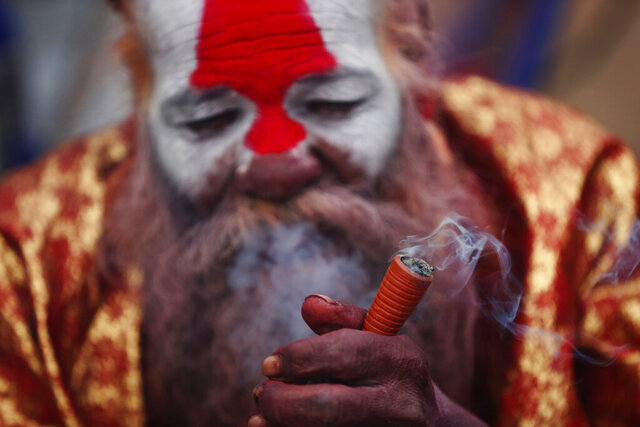 "A Hindu holy man smokes marijuana during Shivaratri festival at the premises of Pashupatinath temple in Kathmandu, Nepal, Friday, Feb. 21, 2020. Hindu holy men were joined by devotees and the public Friday at a revered temple in Kathmandu where they lit up marijuana cigarettes during an annual festival despite prohibition and warning by authorities. Hindu holy men were joined by devotees and the public Friday at a revered temple in Kathmandu where they lit up marijuana cigarettes during an annual festival despite prohibition and warning by authorities. ""There is a ban on smoking marijuana but at the same time it is centuries-old tradition which we have to respect,""said police officer Suman Khadka adding there was no arrests made Friday. (AP Photo/Niranjan Shrestha)"