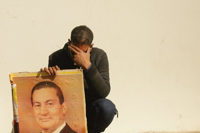 A supporter holds a photo of Egypt's ousted autocratic President Hosni Mubarak as he weeps outside the gate of the mosque ahead of his funeral in New Cairo, Egypt, Wednesday, Feb. 26, 2020. Egypt is holding a full-honors military funeral for Mubarak who was ousted from power in the 2011 Arab Spring uprising. Mubarak, 91, died on Tuesday at a Cairo military hospital from heart and kidney complications. (AP Photo/Maya Alleruzzo)
