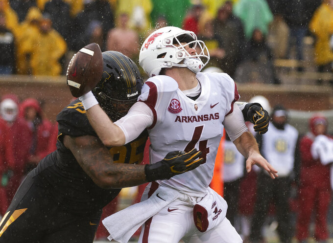 Arkansas quarterback Ty Storey, right, fumbles the ball as he is hit by Missouri defensive lineman Jordan Elliott, left, during the first half of an NCAA college football game Friday, Nov. 23, 2018, in Columbia, Mo. (AP Photo/L.G. Patterson)