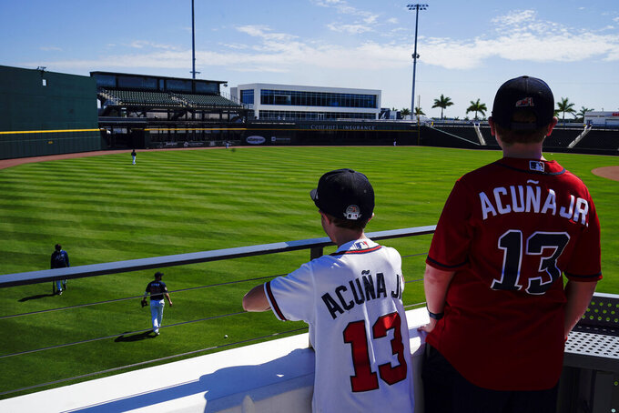 A few fans watch the Atlanta Braves play in the outfield during spring training baseball practice on Tuesday, Feb. 23, 2021, in North Port, Fla. (AP Photo/Brynn Anderson)