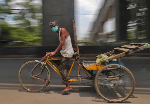 A rickshaw puller wearing a face mask as a precaution against the coronavirus pedals through a street in Hyderabad, India, Wednesday, Sept. 9, 2020. India's coronavirus cases are now the second-highest in the world and only behind the United States. (AP Photo/Mahesh Kumar A.)