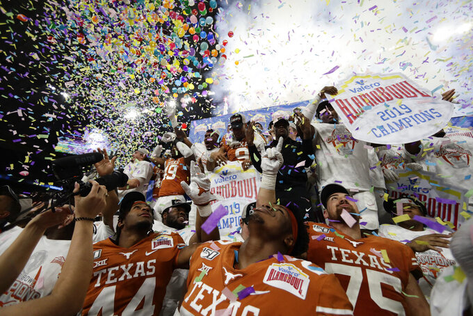 Texas players celebrate their win over Utah in the Alamo Bowl NCAA college football game in San Antonio, Tuesday, Dec. 31, 2019. (AP Photo/Eric Gay)