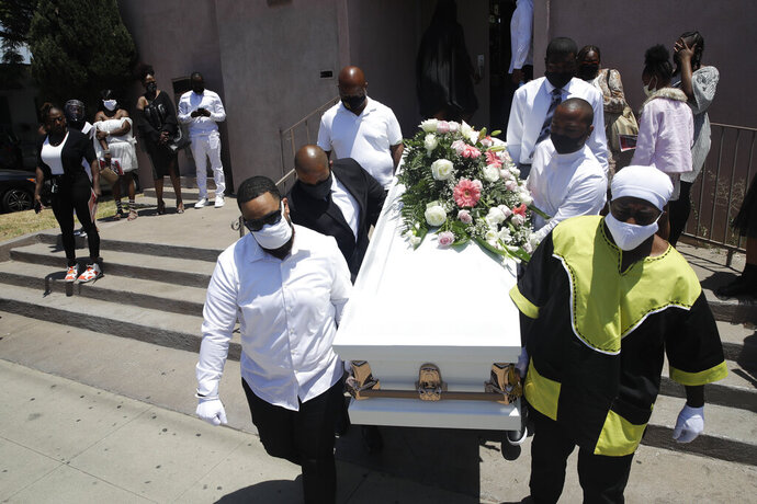 FILE - In this July 21, 2020, file photo, pall bearers carry a casket with the body of Lydia Nunez, who died from COVID-19, after a funeral service at the Metropolitan Baptist Church in Los Angeles. The U.S. death toll from the coronavirus has eclipsed 400,000 in the waning hours in office for President Donald Trump, whose handling of the crisis has been judged by public health experts to be a singular failure. (AP Photo/Marcio Jose Sanchez, File)
