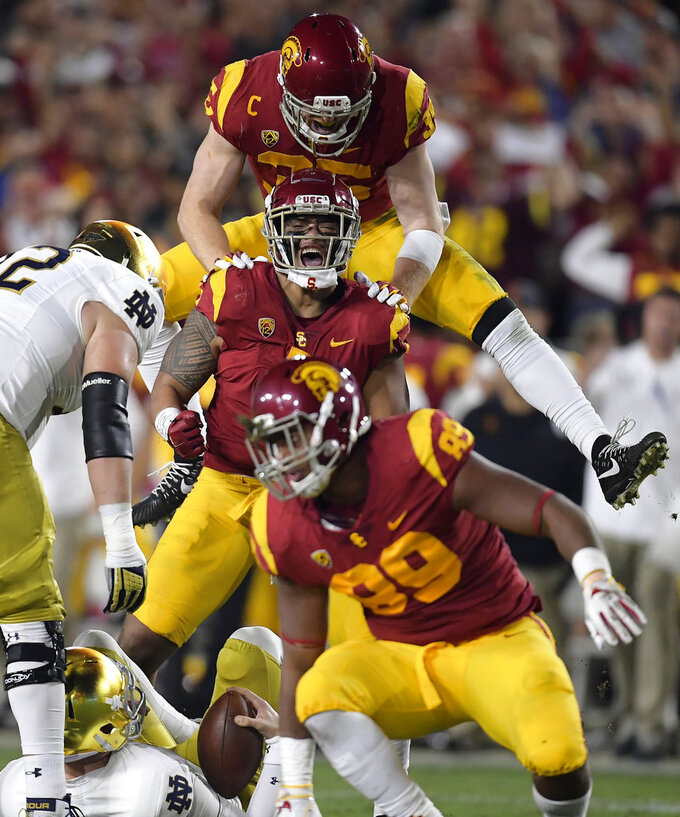Southern California linebacker Palaie Gaoteote IV, second from top, celebrates after sacking Notre Dame quarterback Ian Book, below, with linebacker Cameron Smith, top, and defensive lineman Christian Rector, second from bottom, stands up during the first half of an NCAA college football game Saturday, Nov. 24, 2018, in Los Angeles. (AP Photo/Mark J. Terrill)