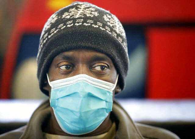 Michael Fowler wears a face mask while waiting for a Tulsa Transit bus at the Denver Avenue Station Tuesday, March 10, 2020. Fowler had the flu recently and said he really doesn't want to get sick again. He wants to be ready and ward off the coronavirus. (Mike Simons/Tulsa World via AP)