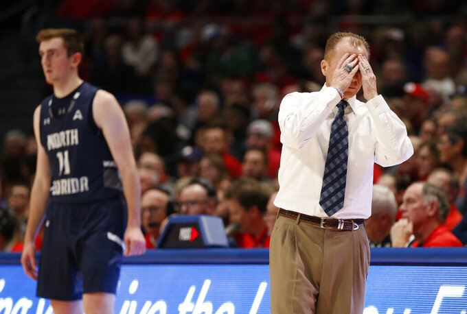 North Florida head coach Matthew Driscoll, right, reacts during the first half of an NCAA college basketball game against Dayton, Monday, Dec. 30, 2019, in Dayton. (AP Photo/Gary Landers)