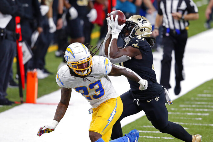 New Orleans Saints running back Alvin Kamara pulls in a recession for a first down over Los Angeles Chargers strong safety Rayshawn Jenkins (23), setting up a touchdown, in the second half of an NFL football game in New Orleans, Monday, Oct. 12, 2020. (AP Photo/Butch Dill)