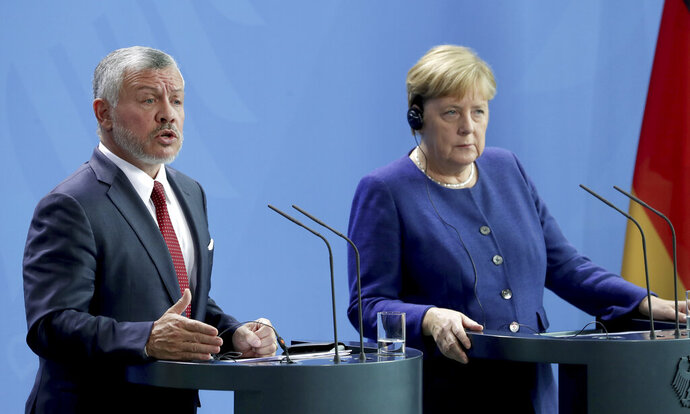 German Chancellor Angela Merkel, right, and Jordan's King Abdullah II, left, address the media during a joint press conference after a meeting at the Chancellery in Berlin, Germany, Tuesday, Sept. 17, 2019. (AP Photo/Michael Sohn)