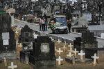Relatives attend the burial of 71-year-old Jose Abelardo Bezerra, who died from COVID-19 related complications, at the Inhauma cemetery in Rio de Janeiro, Brazil, Thursday, Jan. 7, 2021. (AP Photo/Bruna Prado)