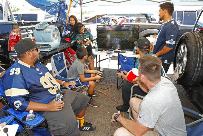 Tailgaters play a football video game before a preseason NFL football game between the Dallas Cowboys and the Los Angeles Rams, Saturday, Aug. 17, 2019, in Honolulu. (AP Photo/Marco Garcia)
