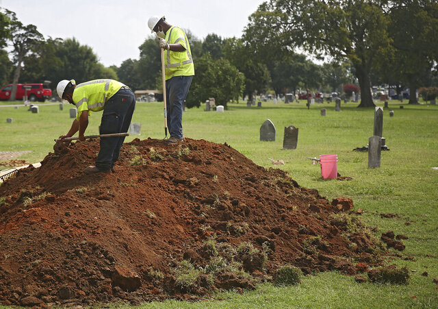 City of Tulsa employees work at Oaklawn Cemetery during a test excavation in the search for possible mass graves from the 1921 Tulsa Race Massacre Tuesday, July 21, 2020. (Mike Simons/Tulsa World via AP)