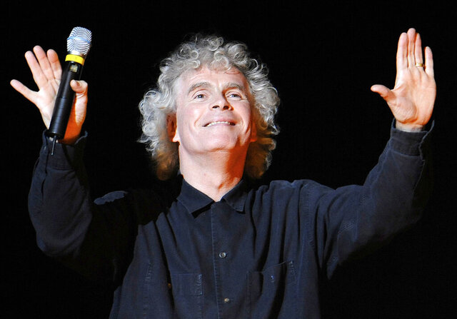 FILE - In this March 27, 2010 file photo, conductor Sir Simon Rattle gestures prior to a dress rehearsal for Richard Wagner's opera