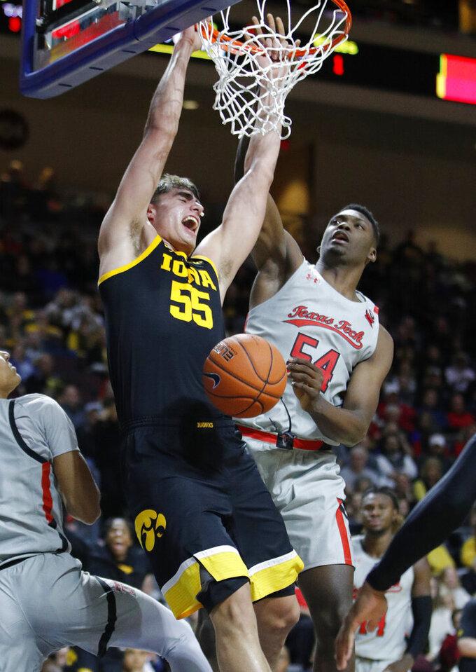 Iowa's Luka Garza (55) dunks against Texas Tech's Russel Tchewa (54) during the second half of an NCAA college basketball game Thursday, Nov. 28, 2019, in Las Vegas. (AP Photo/John Locher)