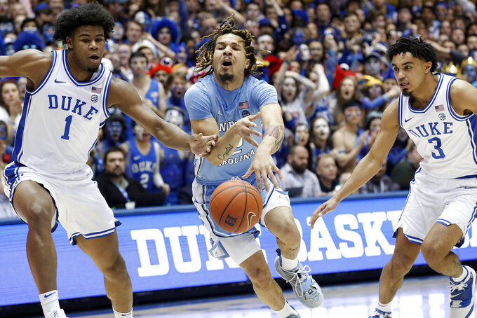 Duke center Vernon Carey Jr. (1) and guard Tre Jones (3) defend against North Carolina guard Cole Anthony during the first half of an NCAA college basketball game in Durham, N.C., Saturday, March 7, 2020. (AP Photo/Gerry Broome)