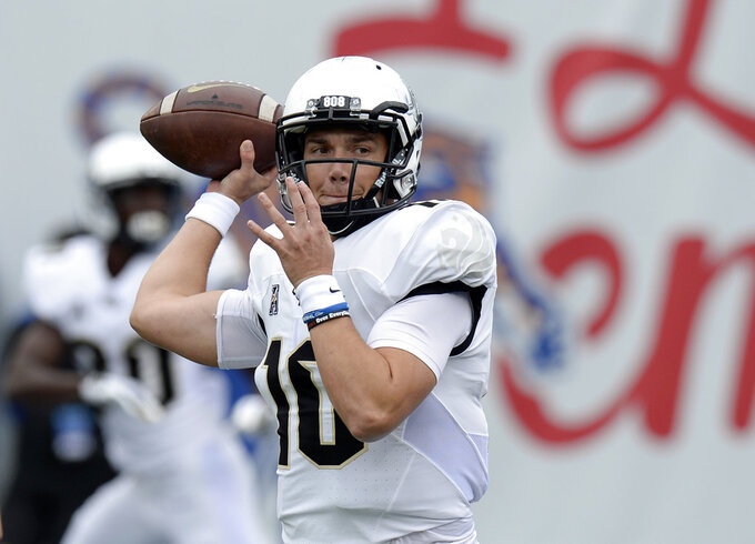 Central Florida quarterback McKenzie Milton warms up before an NCAA college football game against Memphis Saturday, Oct. 13, 2018, in Memphis, Tenn. (AP Photo/Mark Zaleski)