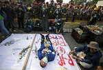 An Indonesian student lies on the ground to symbolize the death of the Corruption Eradication Commission during a rally outside the parliament in Jakarta, Indonesia, Tuesday, Oct. 1, 2019.  Indonesia's Parliament was sworn in Tuesday for a new session that comes amid spasmodic violent anti-government protests. (AP Photo/Dita Alangkara)