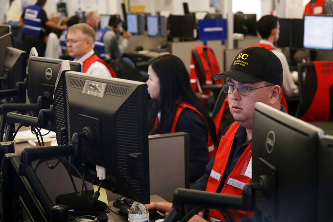 FILE - In this Oct. 10, 2019, file photo, Pacific Gas & Electric employees work in the PG&E Emergency Operations Center in San Francisco. California utility regulators will hear from the state's largest electricity providers over steps taken to mitigate the use of planned power shutoffs, which regulators say should be used only as a last resort to prevent wildfires sparking from utility equipment. San Diego Gas & Electric is briefing the Public Utilities Commission on Monday, Aug. 2, with Southern California Edison and Pacific Gas & Electric up Tuesday. (AP Photo/Jeff Chiu, File)