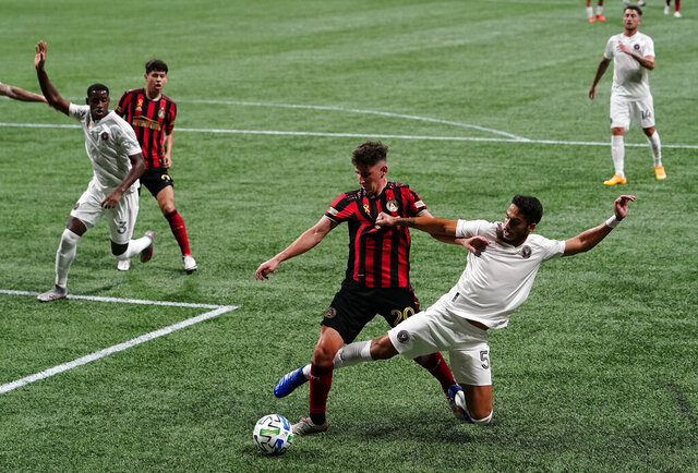Atlanta United midfielder Emerson Hyndman, left, and Inter Miami defender Nicolas Figal, right, fight for the ball during the second half of an MLS soccer match on Wednesday, Sept. 2, 2020, in Atlanta. (AP Photo/Brynn Anderson)