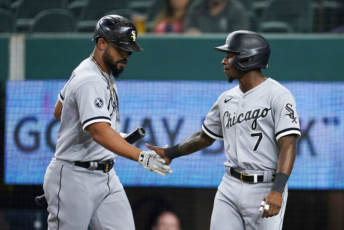 Chicago White Sox's Jose Abreu, left, and Tim Anderson celebrate after Anderson scored on a sacrifice fly by Abreu during the first inning of the team's baseball game against the Texas Rangers in Arlington, Texas, Friday, Sept. 17, 2021. (AP Photo/Tony Gutierrez)