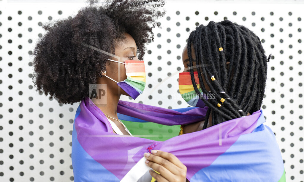 Young lesbian couple wrapped in pride flag during COVID-19