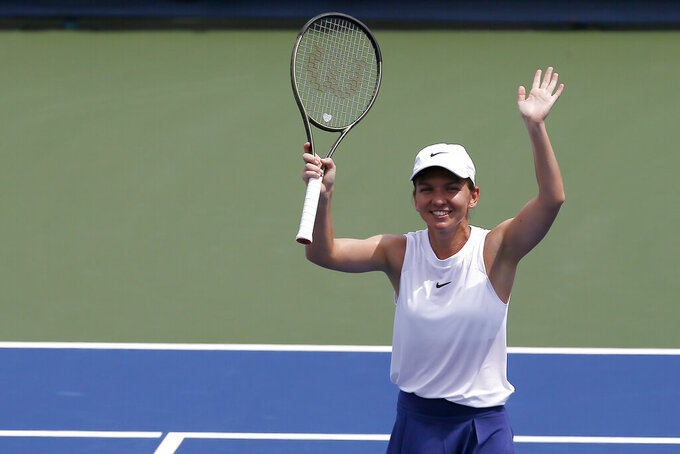 Simona Halep thanks the crowd after defeating Magda Linette to advance in the Western & Southern Open tennis tournament in Mason, Ohio, Tuesday, Aug. 17, 2021. Halep won 6-4, 3-6, 6-1. (Sam Greene/The Cincinnati Enquirer via AP)
