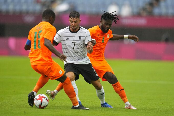 Germany's Marco Richter, center, compete for the ball against Ivory Coast's Max Gradel, left, and Diallo during a men's soccer match at the 2020 Summer Olympics, Wednesday, July 28, 2021, in Rifu, Japan. (AP Photo/Andre Penner)
