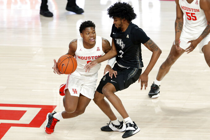 Houston guard Marcus Sasser, left, drives around Central Florida forward Isaiah Adams (3) during the first half of an NCAA college basketball game Sunday, Jan. 17, 2021, in Houston. (AP Photo/Michael Wyke)
