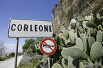 """FILE -- In this file photo taken on April 12, 2006, a road sign announces the town of Corleone, Italy. The Sicilian town of Corleone, made famous by the fictional Mafia clan in """"The Godfather,"""" has ordered schools closed and a limited lockdown after a spate of coronavirus infections were tied to a big wedding there last week. (AP Photo/Luca Bruno)"""