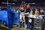 FILE - In this Dec. 1, 2019, file photo, Denver Broncos defensive end Derek Wolfe is helped off the field after getting hunt during the second half of the team's NFL football game against the Los Angeles Chargers in Denver. Wolfe's career year is finished and his eight-season stay in Denver might be over, too. The Broncos placed Wolfe on injured reserve Tuesday, 48 hours after he dislocated his left elbow in a 23-20 win over the Chargers. (AP Photo/Jack Dempsey, File)
