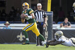Green Bay Packers quarterback Aaron Rodgers, left, scrambles as he is pressured by New Orleans Saints linebacker Tanoh Kpassagnon during the first half of an NFL football game, Sunday, Sept. 12, 2021, in Jacksonville, Fla. (AP Photo/Phelan M. Ebenhack)
