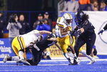 Wyoming running back Xazavian Valladay, center, breaks away from a tackle attempt by Boise State defensive tackle David Moa, right, during the first half of an NCAA college football game Saturday, Nov. 9, 2019, in Boise, Idaho. (AP Photo/Steve Conner)