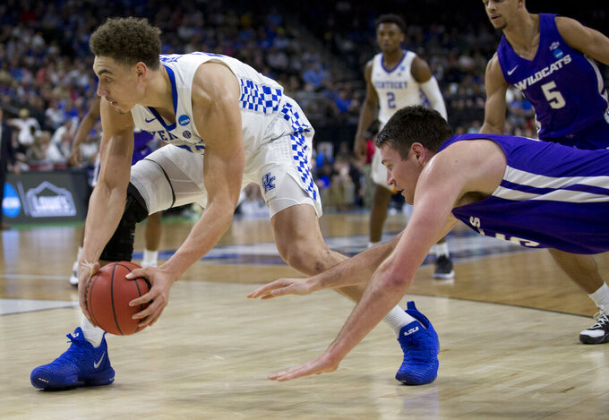 Kentucky's Reid Travis, left, scoops up a loose ball in front of Abilene Christian's Hayden Farquhar during the first half of a first-round game in the NCAA men's college basketball tournament in Jacksonville, Fla., Thursday, March 21, 2019. (AP Photo/Stephen B. Morton)