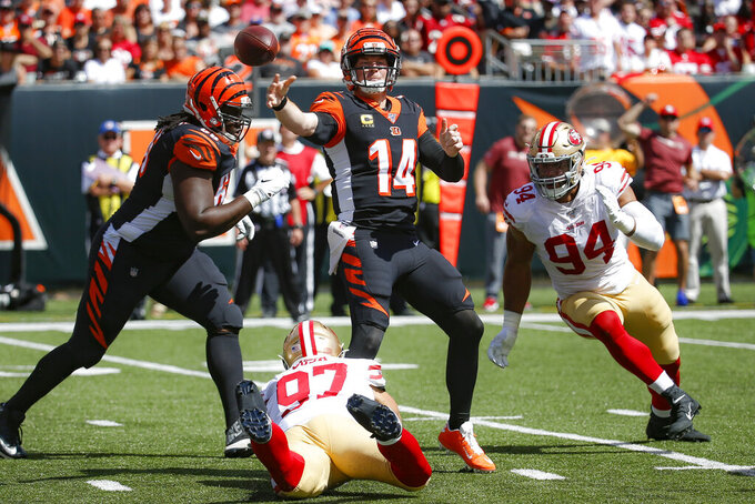 Cincinnati Bengals quarterback Andy Dalton (14) passes under pressure from San Francisco 49ers defensive end Nick Bosa (97) and defensive end Solomon Thomas (94) during the first half an NFL football game, Sunday, Sept. 15, 2019, in Cincinnati. (AP Photo/Frank Victores)